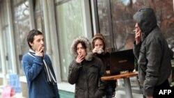 Млади луѓе пушат пред кафе бар