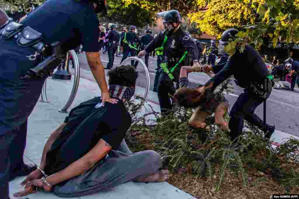 У центрі Лос-Анджелеса, штат Каліфорнія, поліцейські затримують чоловіка, особу якого не встановлено (ліворуч) та Лоріс Терчеро під час акцій пам'яті Джорджа Флойда (який загинув під час затримання поліцейськими), Бреони Тейлор (у березні жінка загинула, після того, як поліцейські увірвались до її будинку з вимогою видати підозрюваного, який вже був під вартою) та на знак солідарності з протестами у Портленді