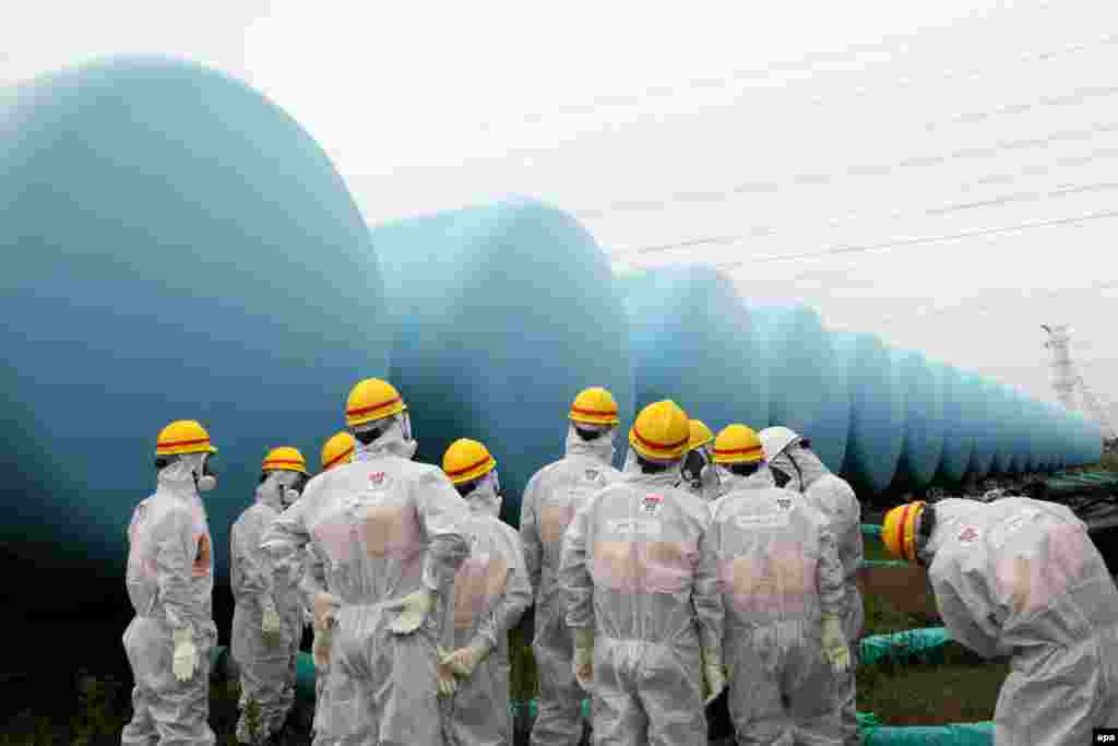 Japan Nuclear Regulation Authority (NRA) employees with protective suits and masks inspect makeshift tanks storing contaminated water at the TEPCO Fukushima Daiichi nuclear power plant.