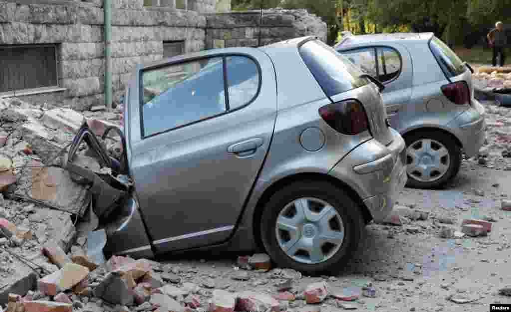 Disa makina të shkatërruara shihen para një ndërtese të dëmtuar në Tiranë.