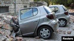 Destroyed cars stand next to a damaged building after an earthquake in Tirana on September 21.