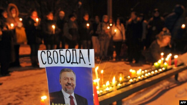 Belarusian opposition supporters light candles near a picture of jailed opposition presidential candidate Andrey Sannikau at a prison's wall during a demonstration in Minsk on December 21.