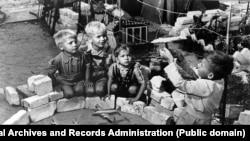 """Дети Западного Берлина, живущие рядом с аэродромом Темпельхоф, играют в """"Берлинский мост"""". Фото 1948 года."""