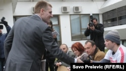 """Premijer Igor Lukšić i članovi MANS-a koji su izveli performans o tome da je Vlada odgovorna za """"prosjački štap"""" na koji je spala većina građana. Podgorica, 1. februar 2012."""