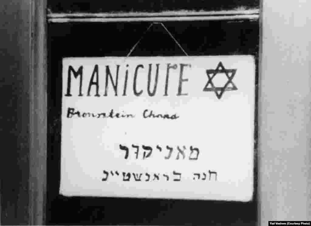 "A store sign says ""Manicure-Chana Branstein."""