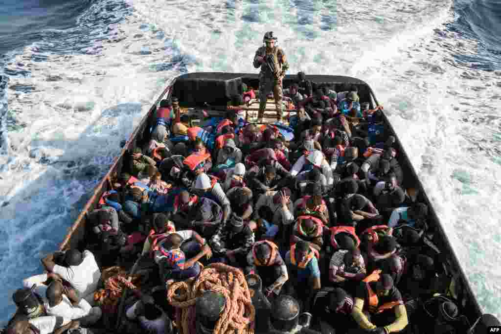 A Libyan coastguard stands on a boat during the rescue of 147 illegal immigrants attempting to reach Europe off the coastal town of Zawiyah, 45 kilometres west of Tripoli, on June 27. (AFP/Taha Jawashi)