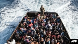 A Libyan coast guardsman stands on a boat during the rescue of 147 illegal immigrants attempting to reach Europe.
