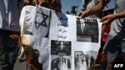 Палестинцы сжигают плакаты во время акции протеста. Рамалла, 22 сентября 2011 года.