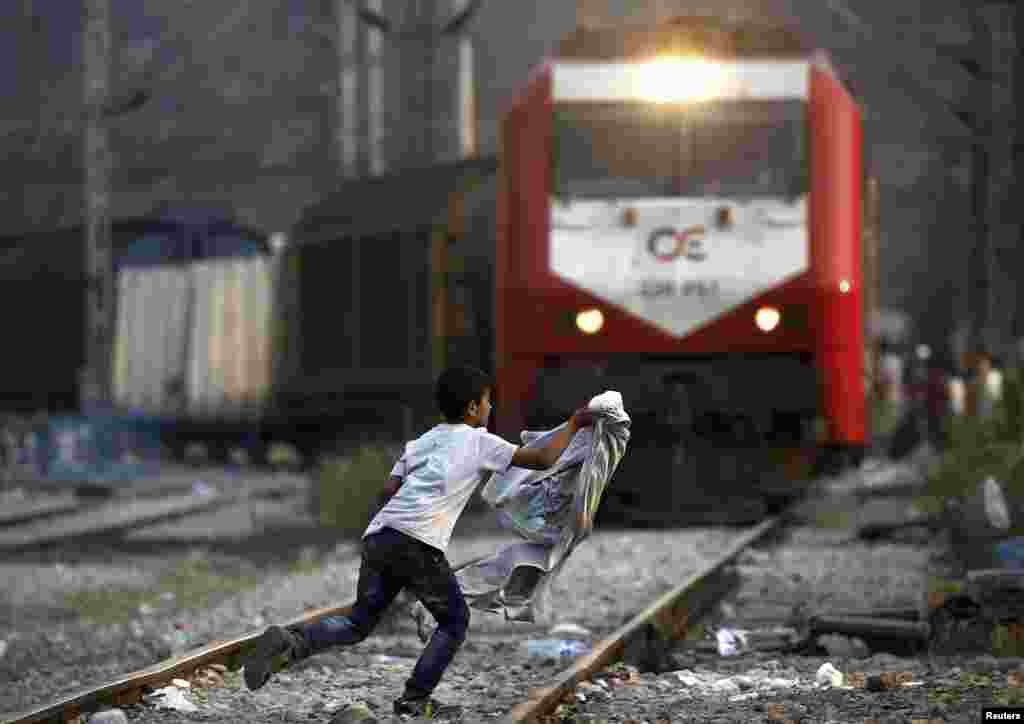 A Syrian refugee boy runs across rail tracks as a freight train approaches near Greece's border with Macedonia, outside the Greek village of Idomeni. (Reuters/Yannis Behrakis)