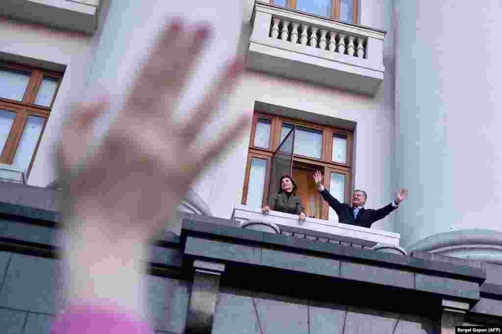 """Outgoing Ukrainian President Petro Poroshenko and his wife, Maryna, greet supporters from the balcony of his office during a """"thank-you"""" rally in Kyiv on April 22. Poroshenko was defeated in a landslide by comedian Volodymyr Zelenskiy in a runoff on April 21. (AFP/Sergei Gapon)"""