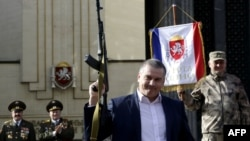 Ukraine -- Russian acting leader of Crimea Sergei Aksyonov holds a Kalashnikov during the celebration of Defender of the Fatherland Day in the Crimean city of Simferopol, February 23, 2015