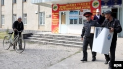 A Kyrgyz election worker carries a ballot box during voting in the town Belovodsk on September 30.