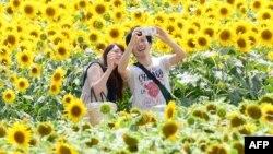 Жастар смартфонмен суретке түсіп жүр. Жапония, 27 маусым 2013 жыл. (Көрнекі сурет)