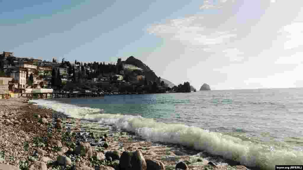 Хвилі перекочуються зігрітою сонцем галькою на пустельному пляжі
