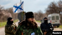 Milutin Malisic, a member of a Serbian Chetnik paramilitary group, and armed members of a local self-defence unit man a checkpoint on the highway between Simferopol and Sevastopol in the Crimean peninsular March 13, 2014