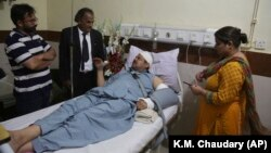 Pakistani TV anchorman Asad Kharal talks to visitors at a hospital in Lahore after he was stabbed by masked men near his residence on June 6.