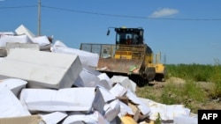 A bulldozer crushing boxes of cheese outside the Russian southern city of Belgorod on August 6, 2015.