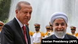 Iranian President Hassan Rohani (right) shakes hands with Turkish President Recep Tayyip Erdogan in Tehran on October 4.