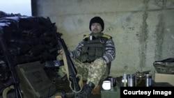Yaponiya. Donbassdagi urush qatnashchisiday kiyingan yapon Kalashnikov avtomati bilan o'tiribdi.