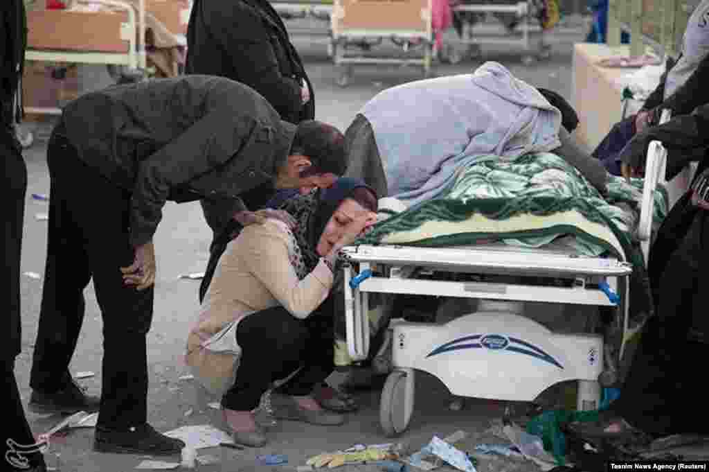 A woman mourns next to a body in Sarpol-e Zahab.