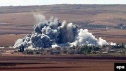 """""""Ислам мемлекетінің"""" Түркия шекарасына жақын маңдағы позициясын бомбалау сәтінен көрінісі. Кобани, 15 қазан 2014 жыл."""