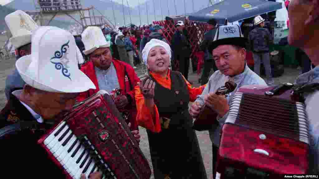 Музыканттармен ән шырқап тұрған әнші
