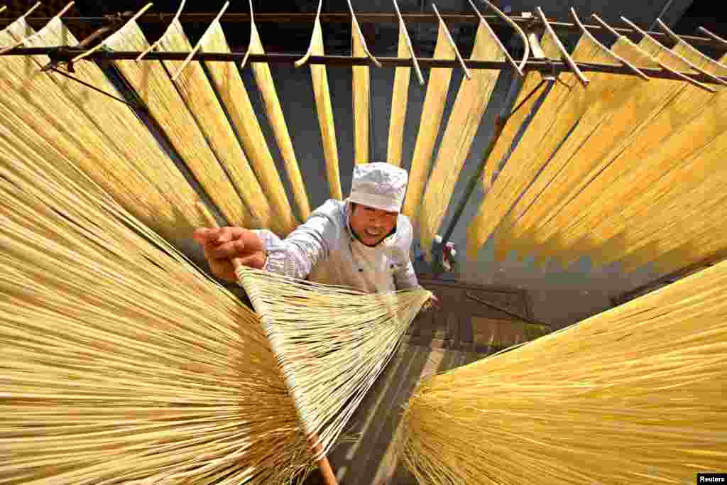 A villager hangs handmade noodles up to dry in Linyi, Shandong Province, China. (Reuters/Stringer)