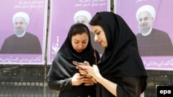 Iranian women stand in front of election posters for President Hassan Rohani in city of Karaj.