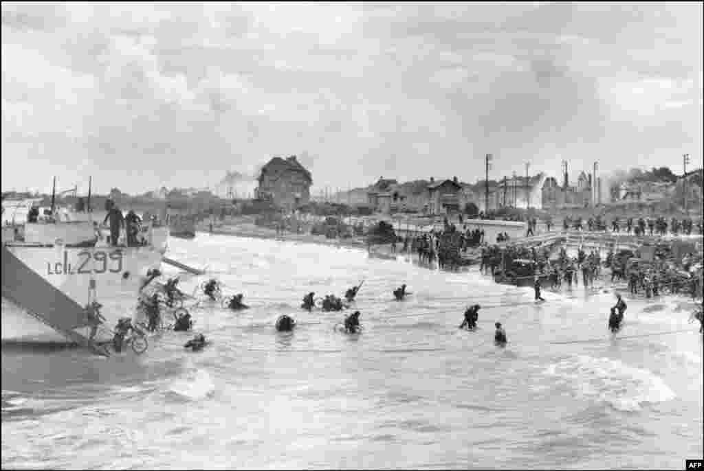 Канадські солдати з 9-ї бригади висадилися 6 червня 1944 року зі своїми велосипедами на пляжі Юно в Берньєр-сюр-Мер під час Дня «Д», а союзні війська штурмують пляжі Нормандії. День «Д»