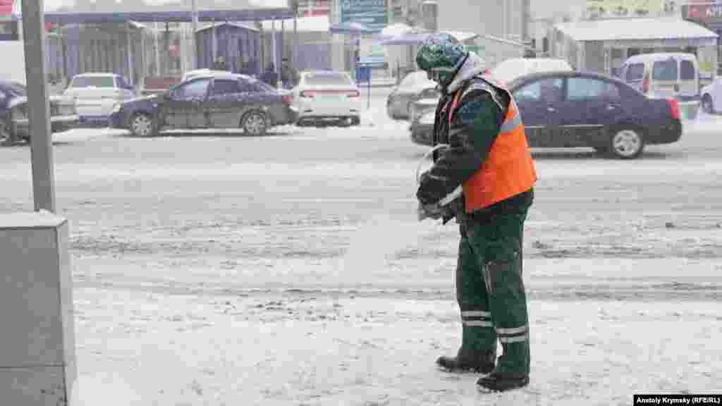 Azbar hızmetçisi Kiyev soqağında avtobus turaqlarındaki qaldırımğa reagent qarışmasını sepe