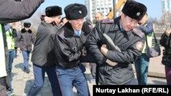 Полиция наразы азаматты көлікке күштеп салуға әкетіп барады. Алматы, 1 наурыз 2020 жыл.