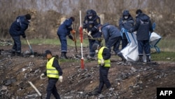 Dutch and Malaysian investigators work at the MH17 plane crash site near the village of Hrabove on April 16.