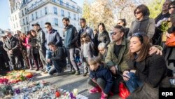 Людзі зьбіраюцца каля канцэртнай залы Bataclan у Парыжы, каб ушанаваць памяць загінулых. Парыж, 15 лістапада 2015 году