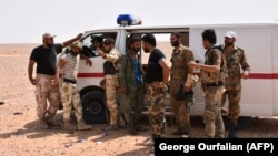 Syrian pro-government forces stand near an ambulance west of Deir al-Zour on September 4.
