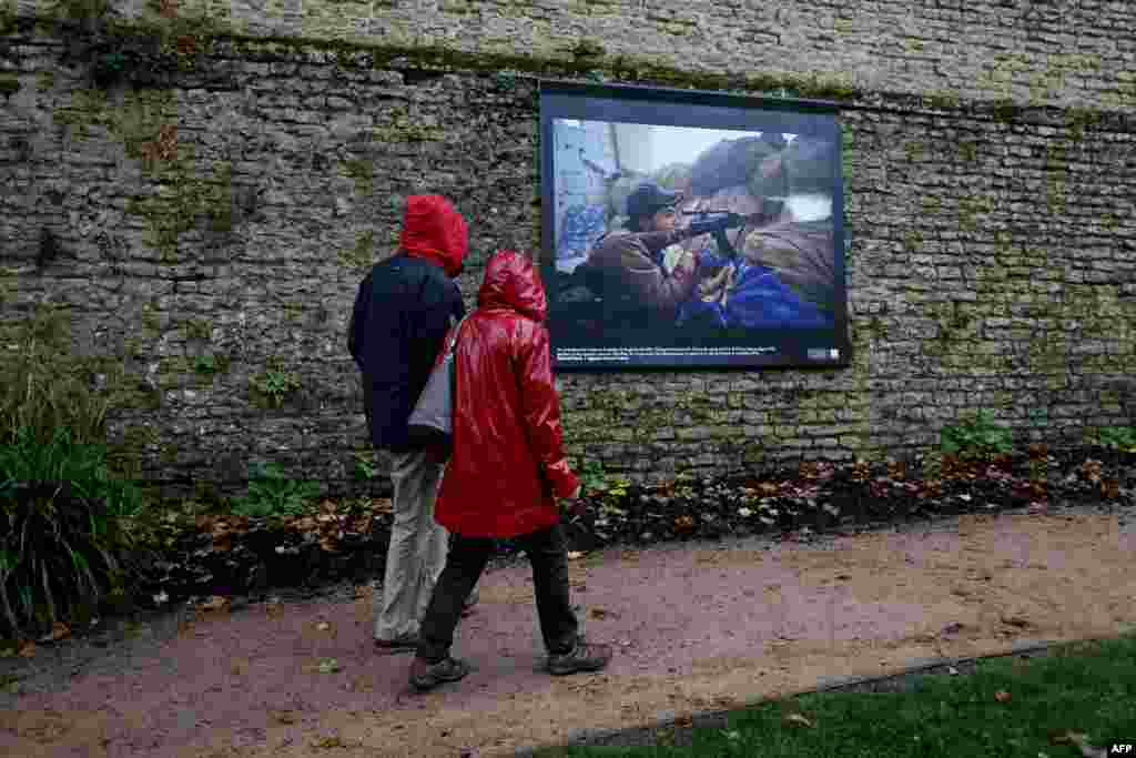 People pass by a photograph by AFP photographer Ahmed Deeb displayed on a street in Bayeux, France, as part of the 22th edition of the Bayeux-Calvados award for war correspondents. (AFP/Charly Triballeau)