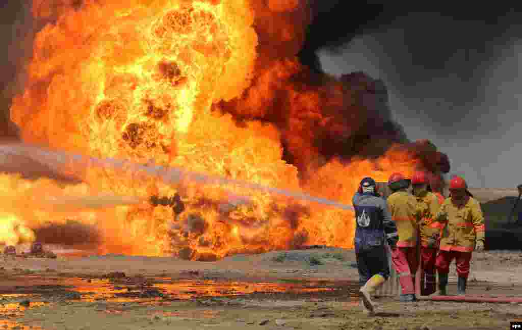 Oil workers and firemen try to extinguish flames at the Khabbaz oil field some 20 kilometers southwest of Kirkuk, Iraq. (epa)