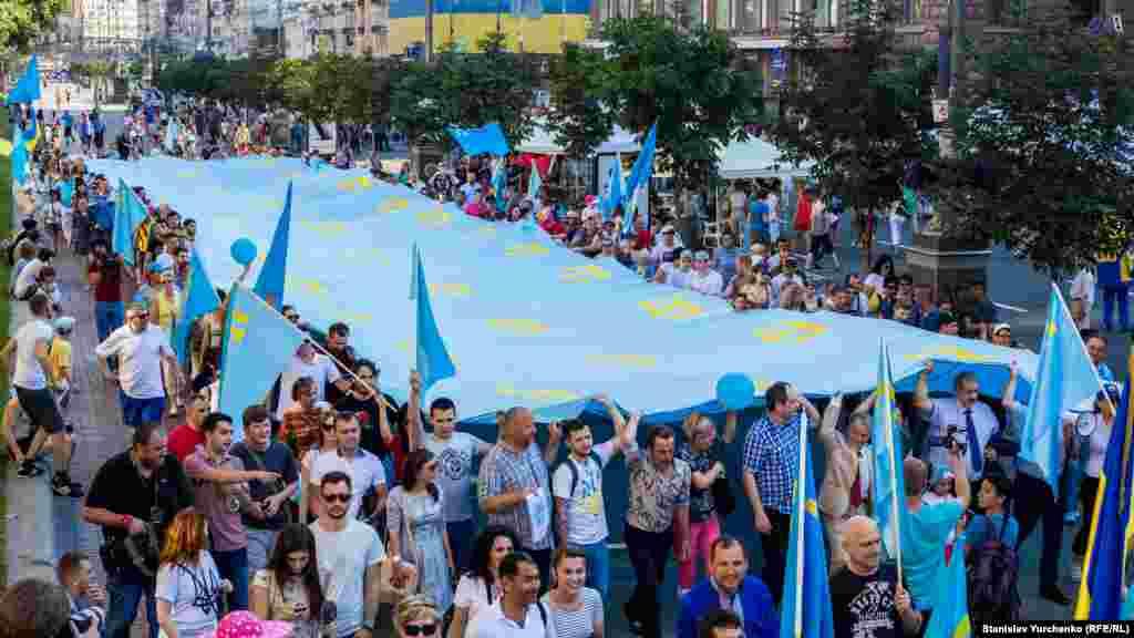 День крымскотатарского флага отметили в столице Украины, 26 июня Несколько сотен активистов прошлись по центру Киева шествием с крымскотатарским флагом длинной 39 метров. По информации организаторов акции, флаг, который они пронесли, является самым большим в мире. Полотнище 6 метров в длину и 39 в ширину, сшитое из 40 мелких флагов, привезли из Турции специально к празднику.