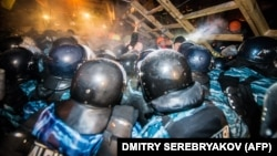 Riot police try to remove a barricade held by protesters on Independence Square in Kyiv early on December 11.