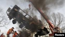 Рабочие убирают сгоревший грузовик, Бишкек, 9 апреля 2010
