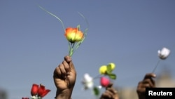 Opposition supporters wave roses during an antigovernment protest in Sanaa on January 26.
