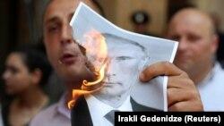 Участник в протестите в Тбилиси в петък е запалил снимка на руския президент.