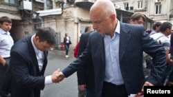 Oleksander Tymoshenko (right) shakes hands with an acquaintance in Kyiv in August.