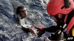 A migrant is rescued from the Mediterranean Sea some 20 nautical miles north of Libya on October 3.