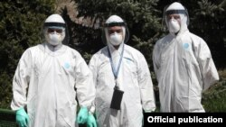 Armenia -- Medical personnel clad in protective gear pose for a photograph outside the Surp Grigor Lusavorich hospital in Yerevan, April 9, 2020.