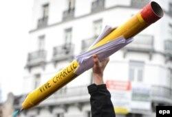 """Участник январского марша солидарности с """"Шарли Эбдо"""" несет символический карандаш"""