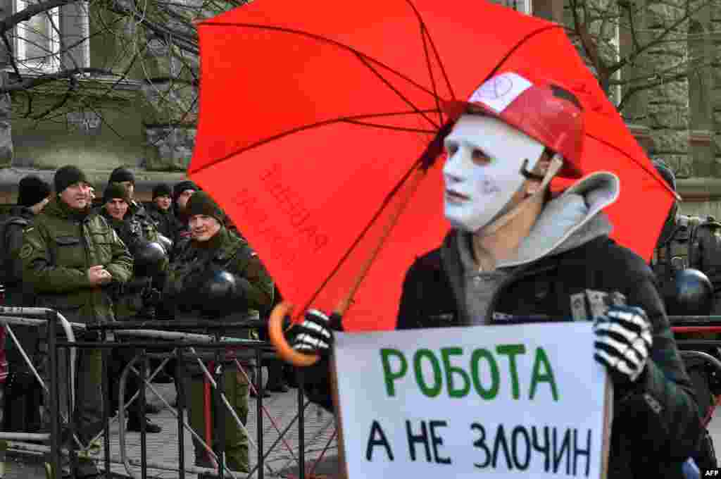 "Policemen smile as a man wearing a mask holds a placard reading ""Worker but not criminal"" during a march of sex workers in Kyiv. (AFP/Serhiy Supinsky)"