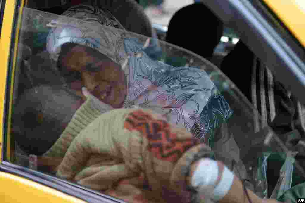 A Syrian woman holds her injured son in a taxi as they arrive at a hospital in the northern city of Aleppo following shelling by government forces. (AFP/Aamir Qureshi)