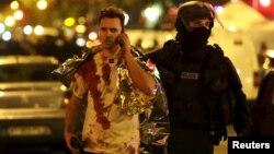 Французький поліцейський допомагає пораненому біля театру «Батаклан». Париж, 14 листопада 2015 року