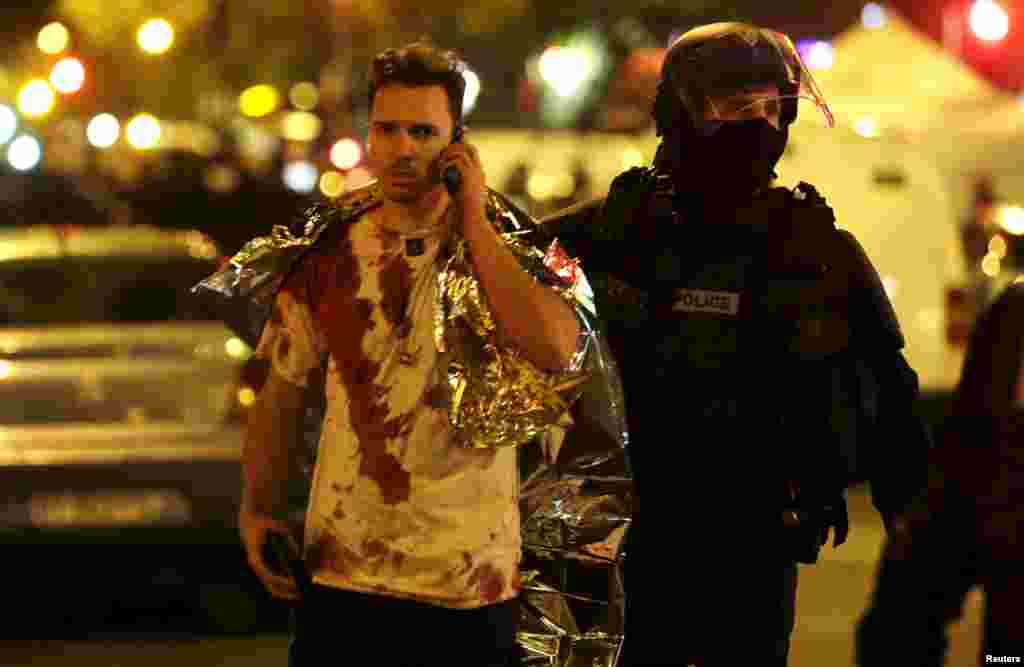 A French policeman assists a blood-soaked victim near the Bataclan concert hall.