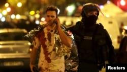 Policajac pomaže momku koji je preživio napad u Bataklanu u Parizu